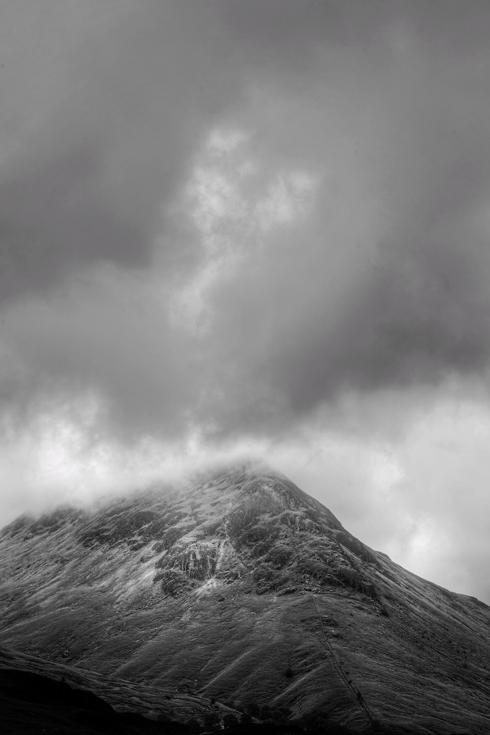 grayscale photography of mountain covered with fogs