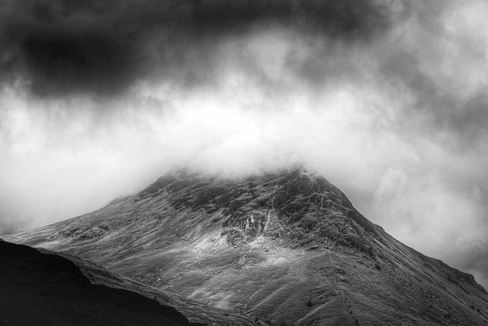 grayscale photo of foggy mountain