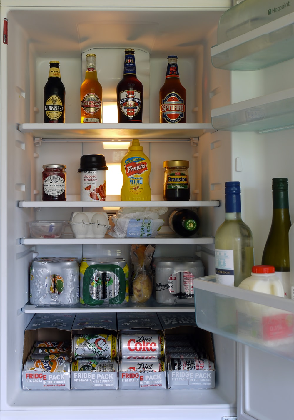 assorted beverage bottles and cans in refrigerator