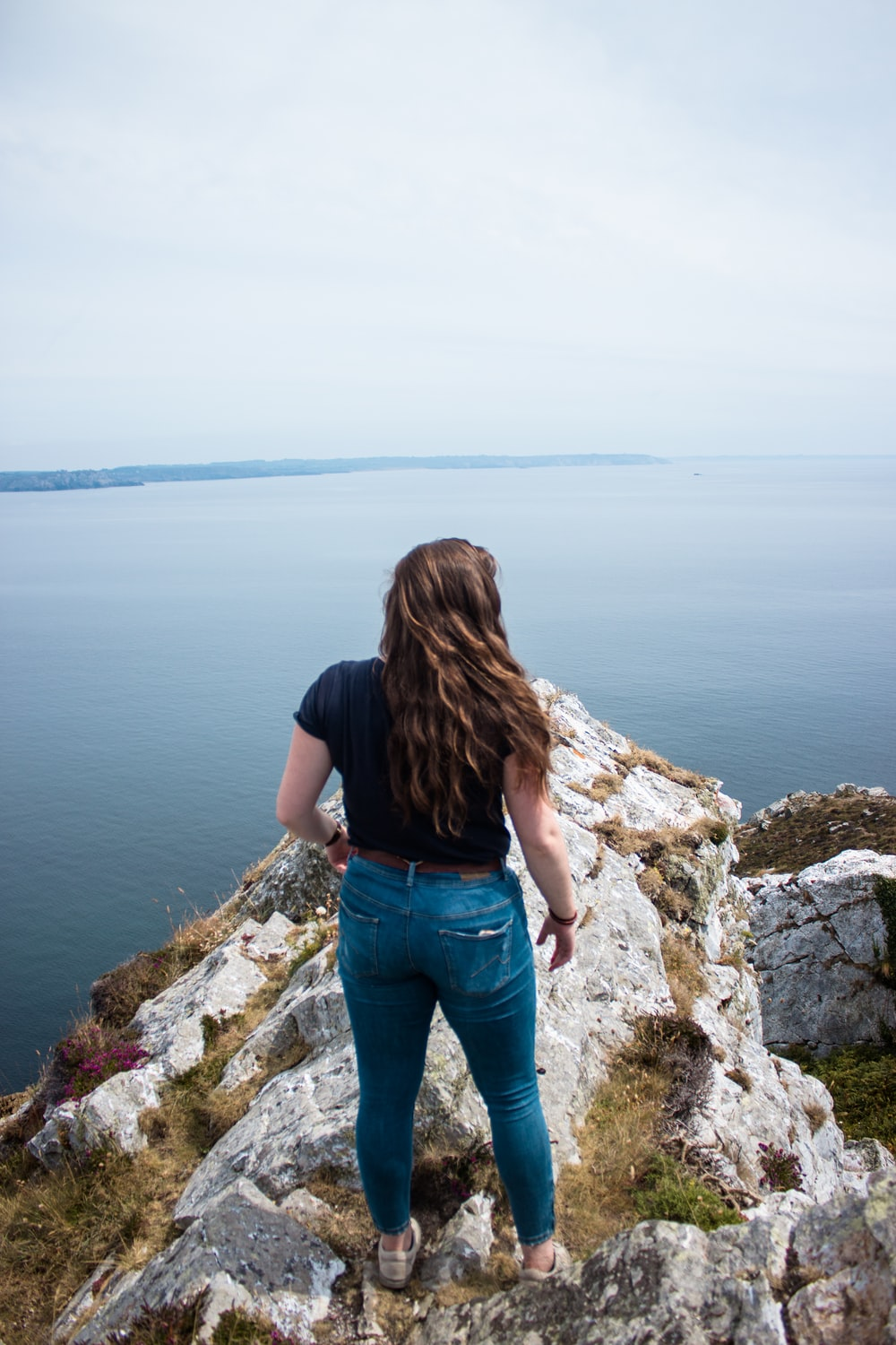 woman wearing black shirt and blue denim jeans standing on rock