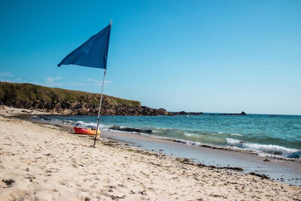 blue flag beside body of water at daytime