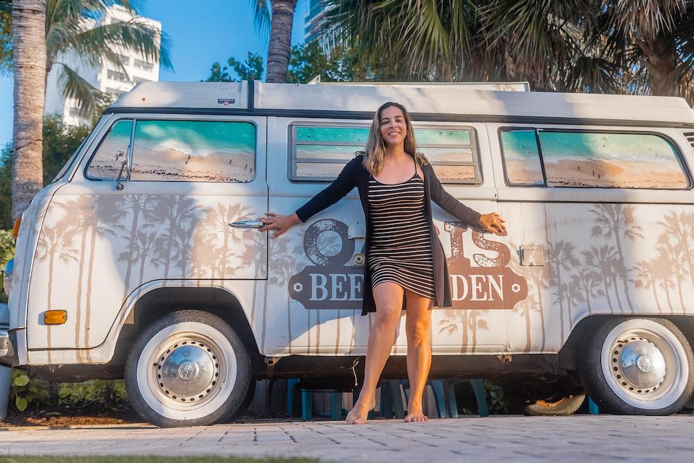 smiling woman standing beside van during daytime
