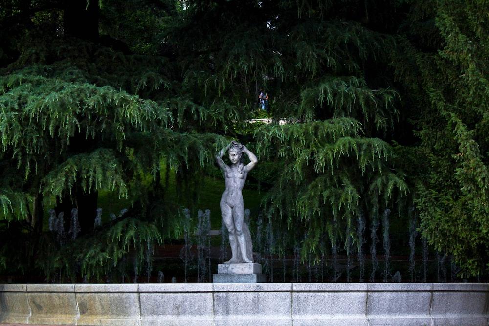 man statue near green trees