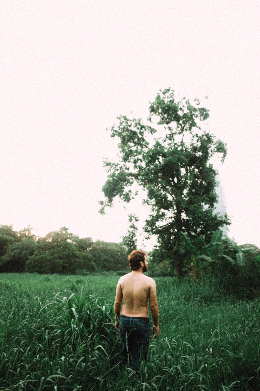 topless man standing near grass field during daytime