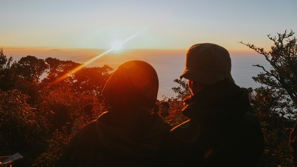 two people on high ground overlooking the sea during sunset