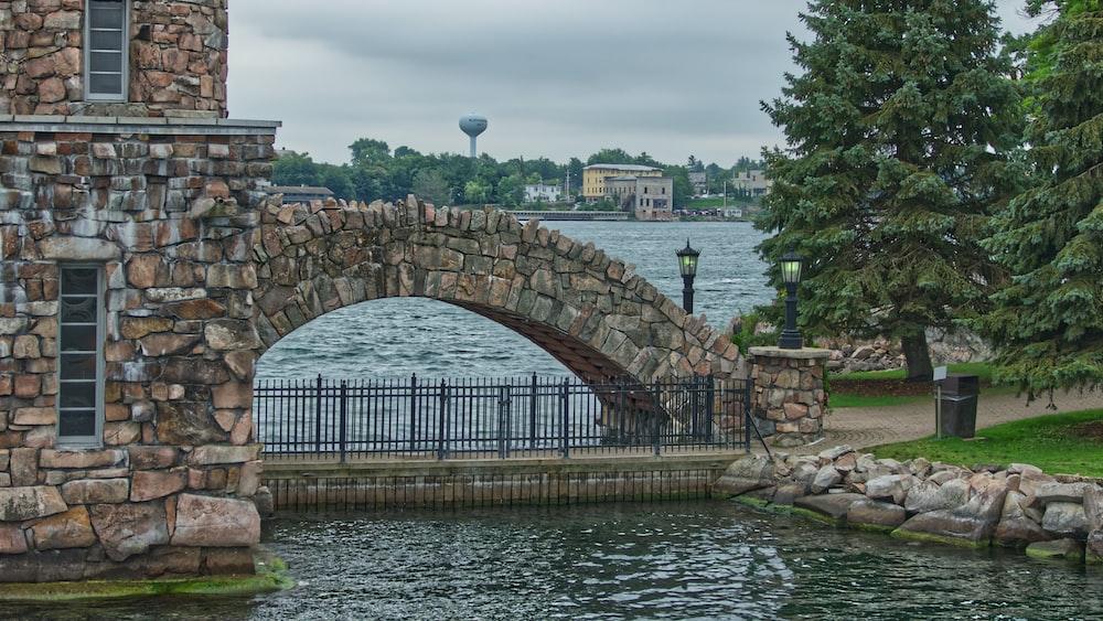 wrought iron fence under arch stone bridge
