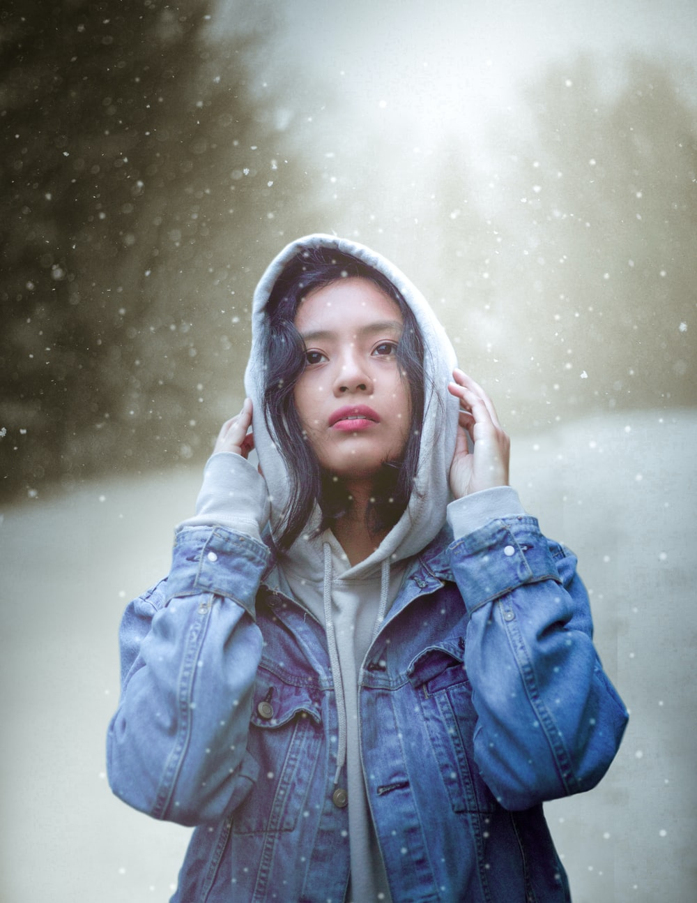 woman standing and wearing blue denim hooded jacket