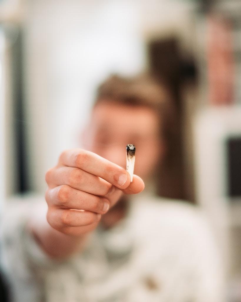 woman holding cigarette butt