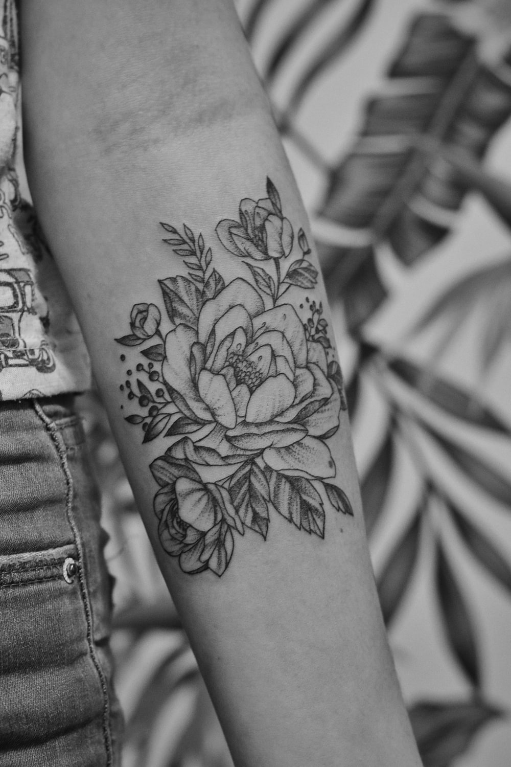 grayscale photo of floral arm tattoo