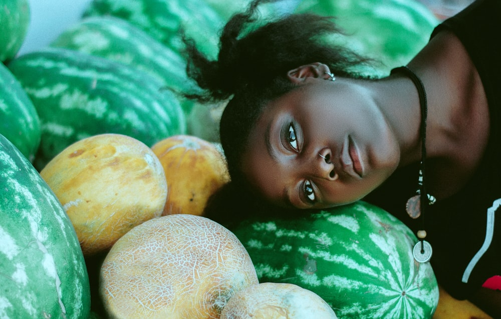 woman wearing black and white shirt leaning head on green watermelon fruits near cantaloupe