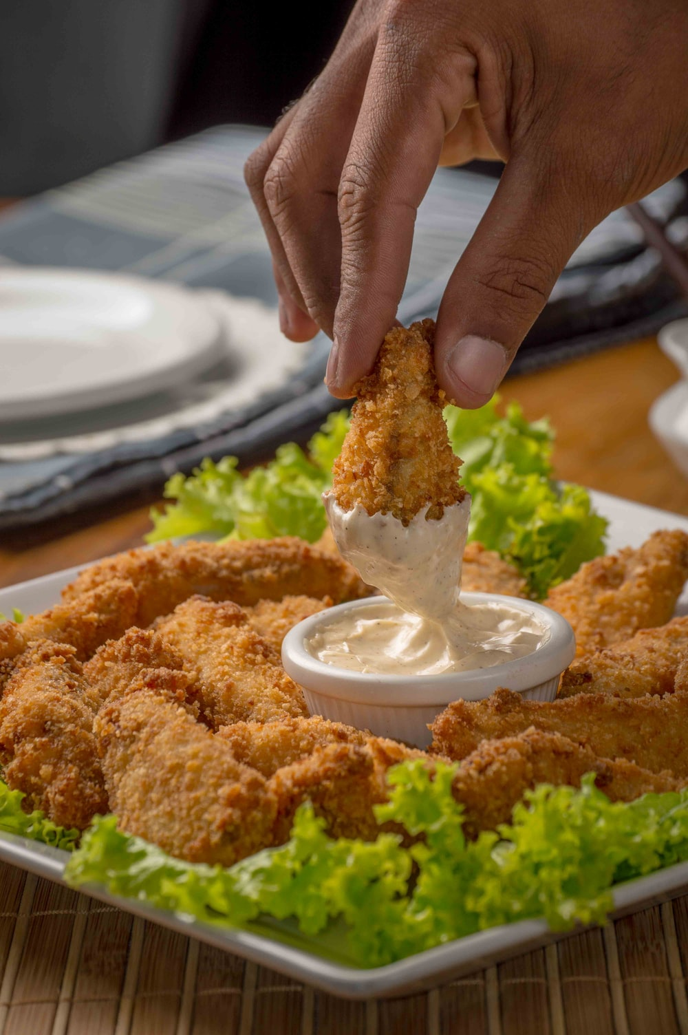 person dipping fried cuisine on dip