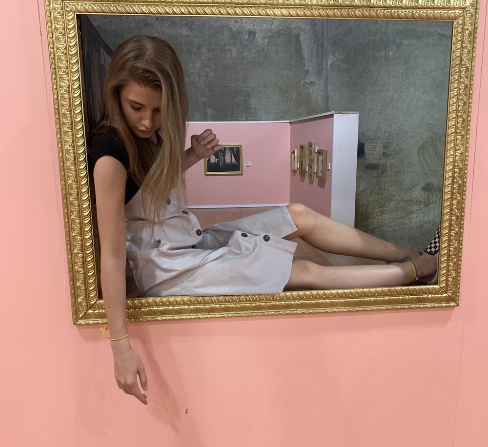 woman sitting on gray and brown painting frame