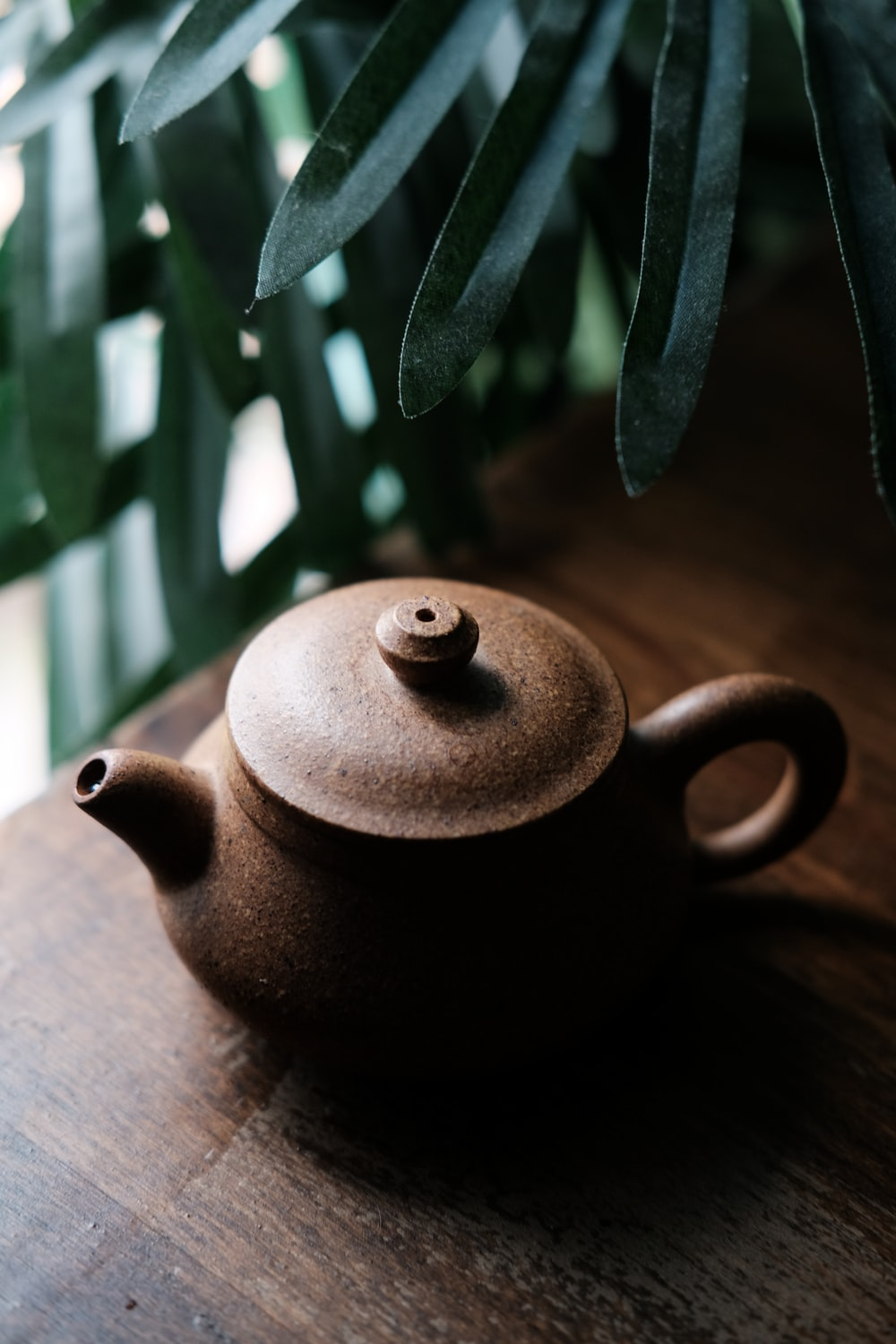brown tea pot on brown wooden surface