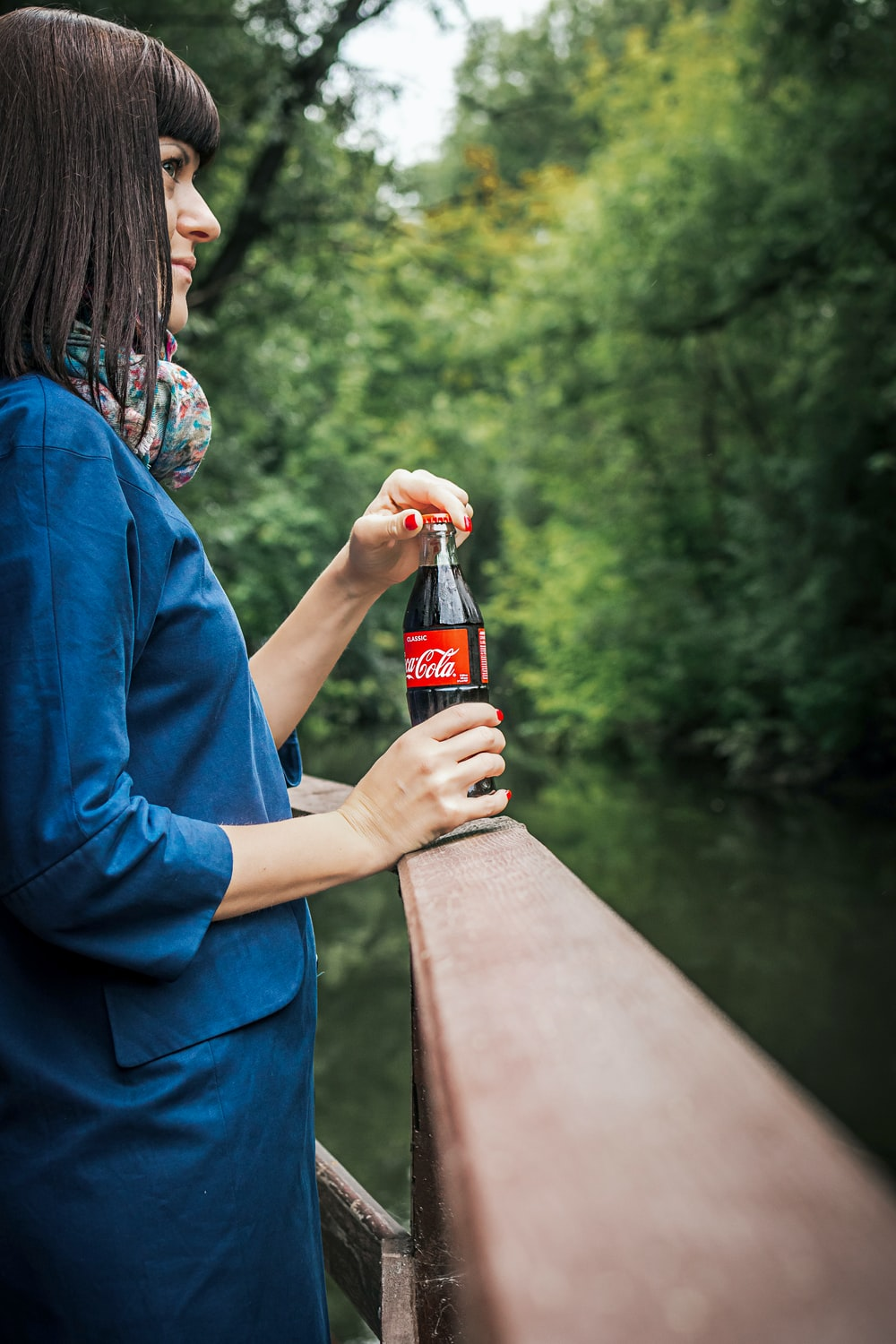 smiling woman standing and holding Coca-Cola soda bottle