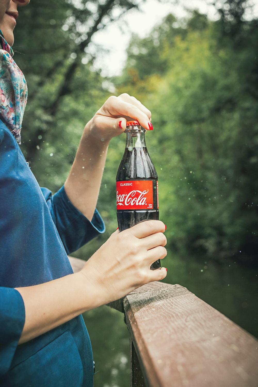 person holding Coca Cola bottle near railings