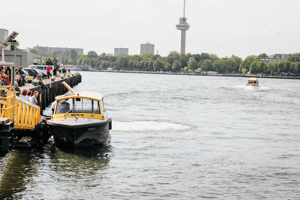 white, black, and yellow boat on body of water