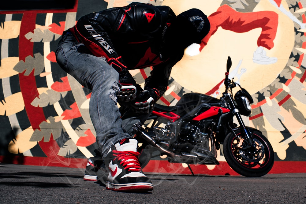 man wearing black and red leather jacket beside naked motorcycle