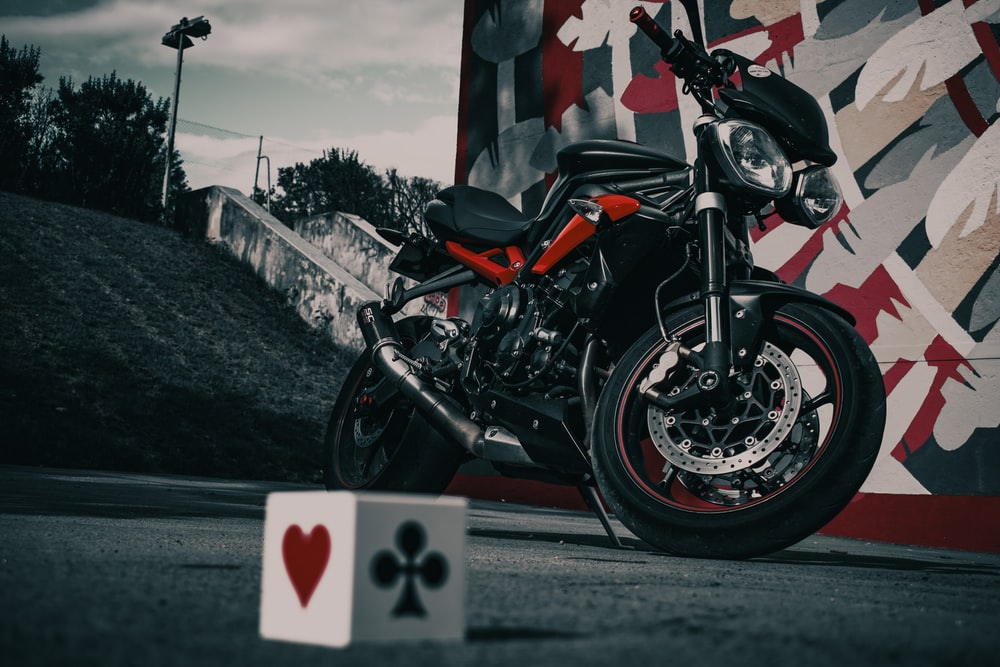 shallow focus photo of black and red naked bike