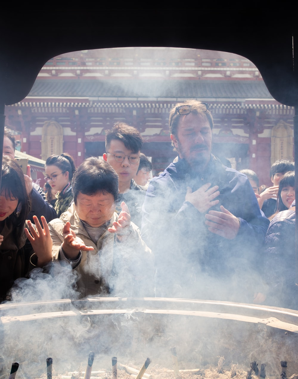 people standing near altar with incenses