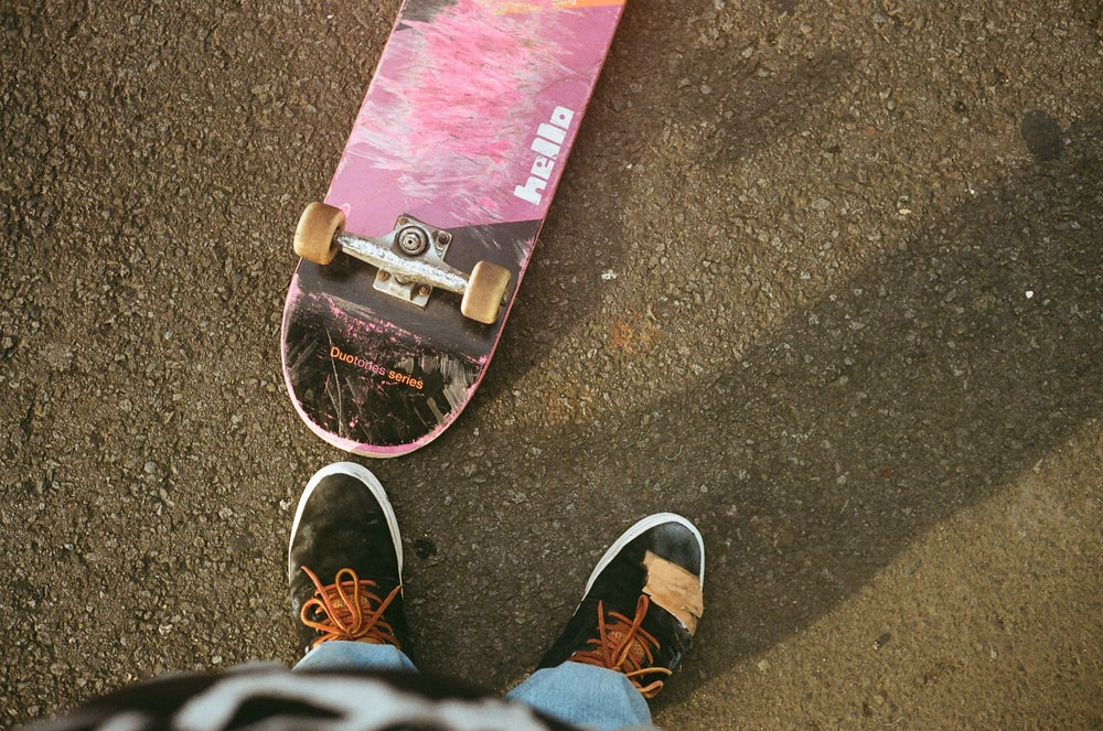 person near pink and black skateboard