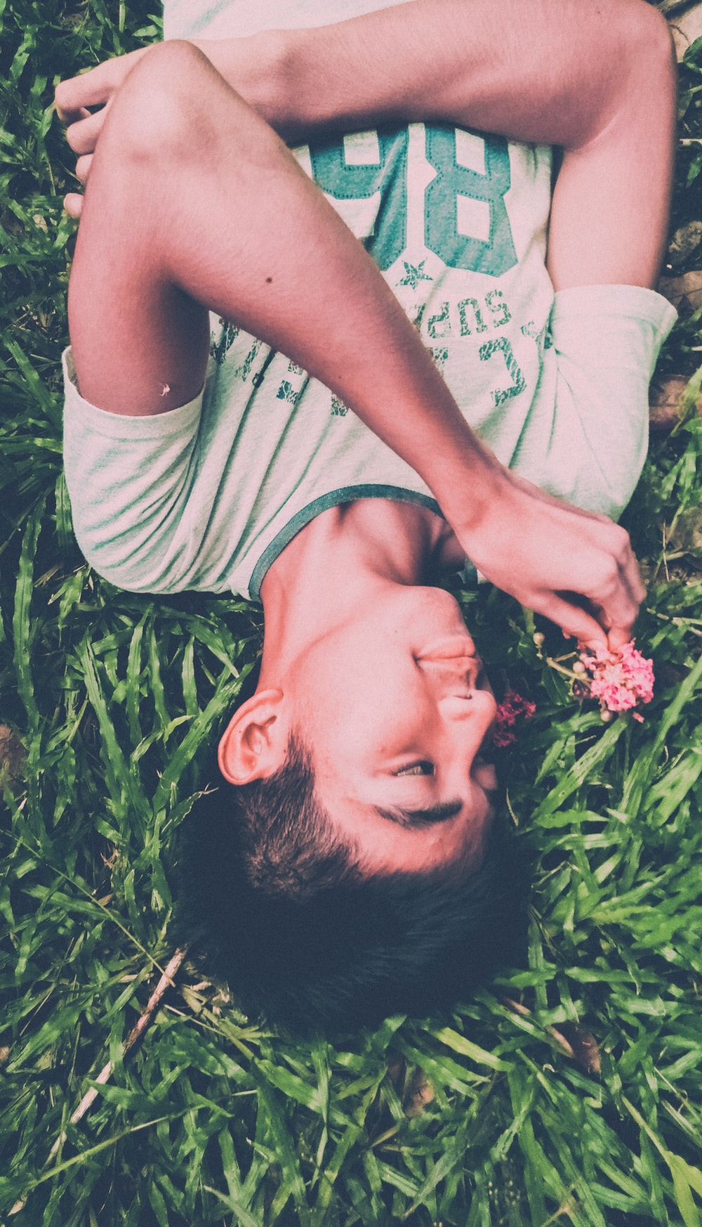boy in white and green crew-neck t-shirt lying on ground