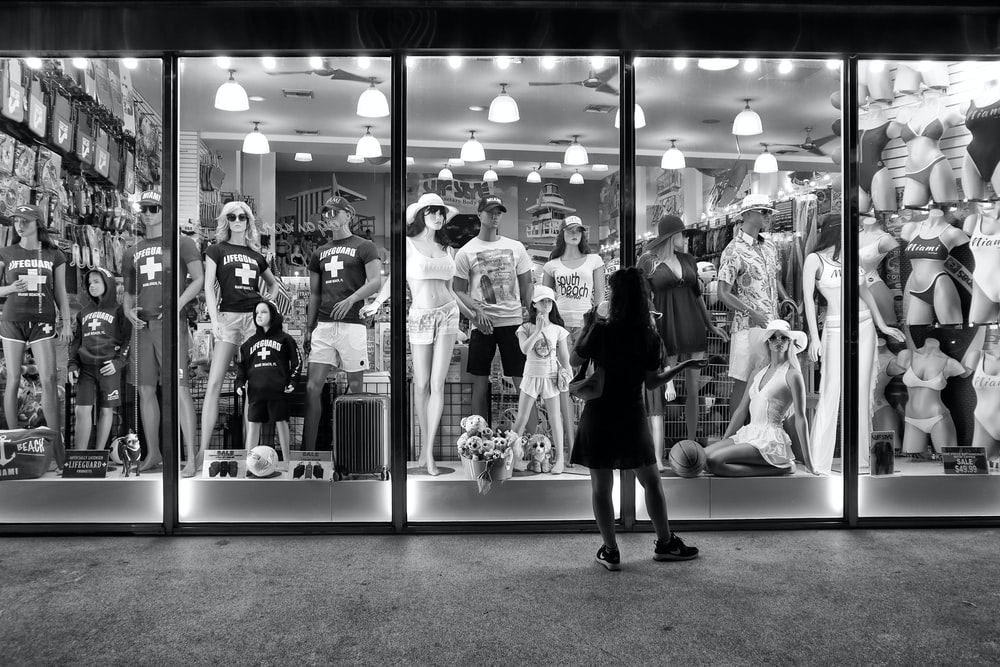 greyscale photography of woman standing outside store