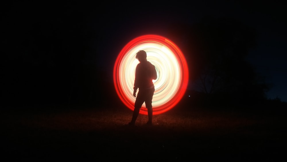 silhouette of man with fire during nigh time