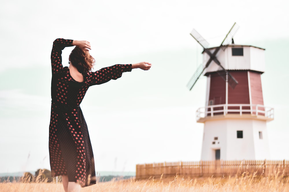 woman walking near windmill