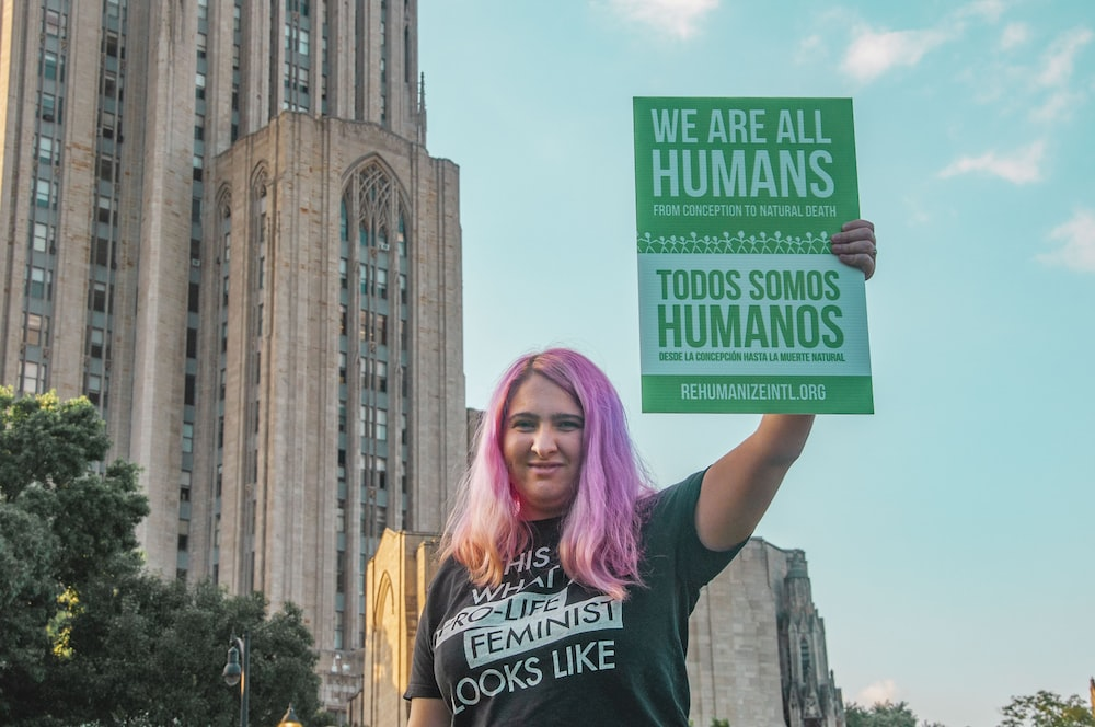 woman wearing black and white printed t-shirt standing while holding banner with we are all human text