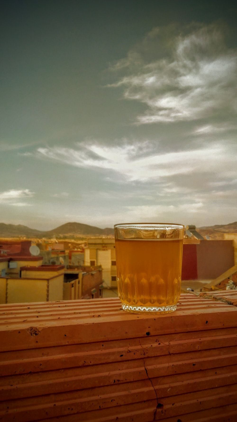 clear pint glass with beer on ledge