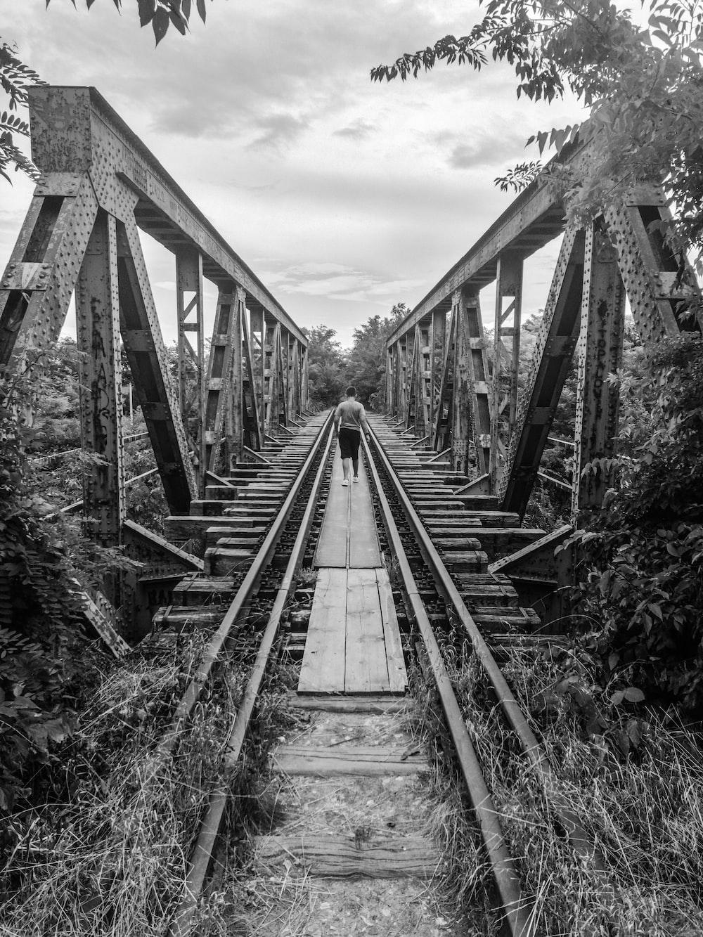 grayscale photography of man on bridge