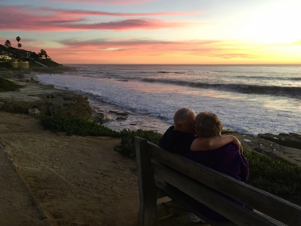 man and woman sitting on brown wooden bench in front of shoreline
