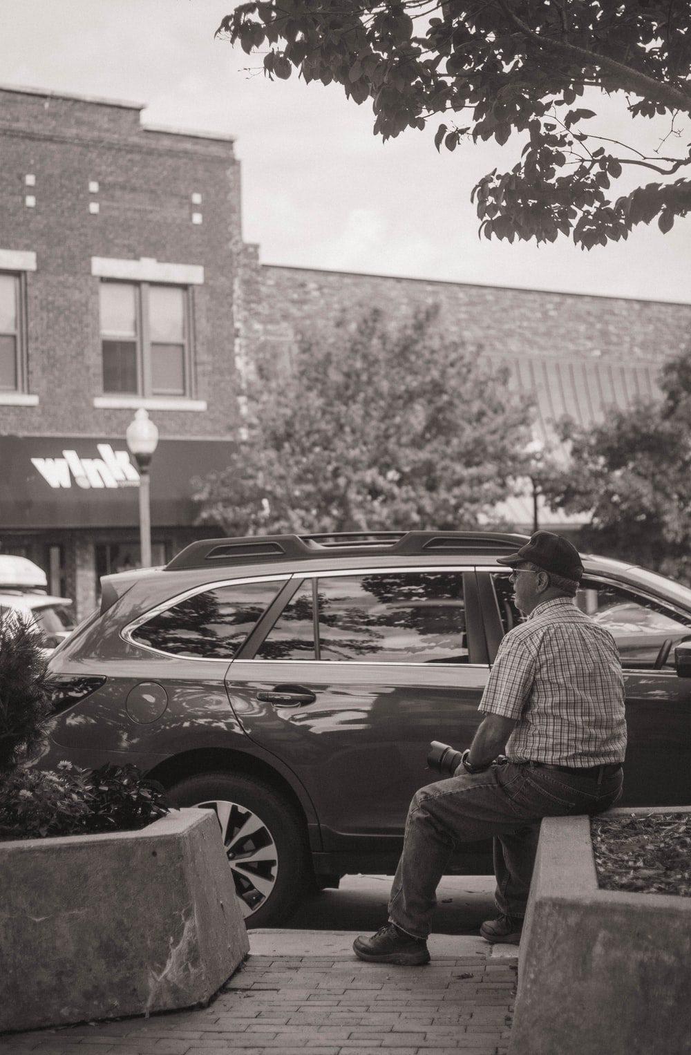 grayscale photography of man siting