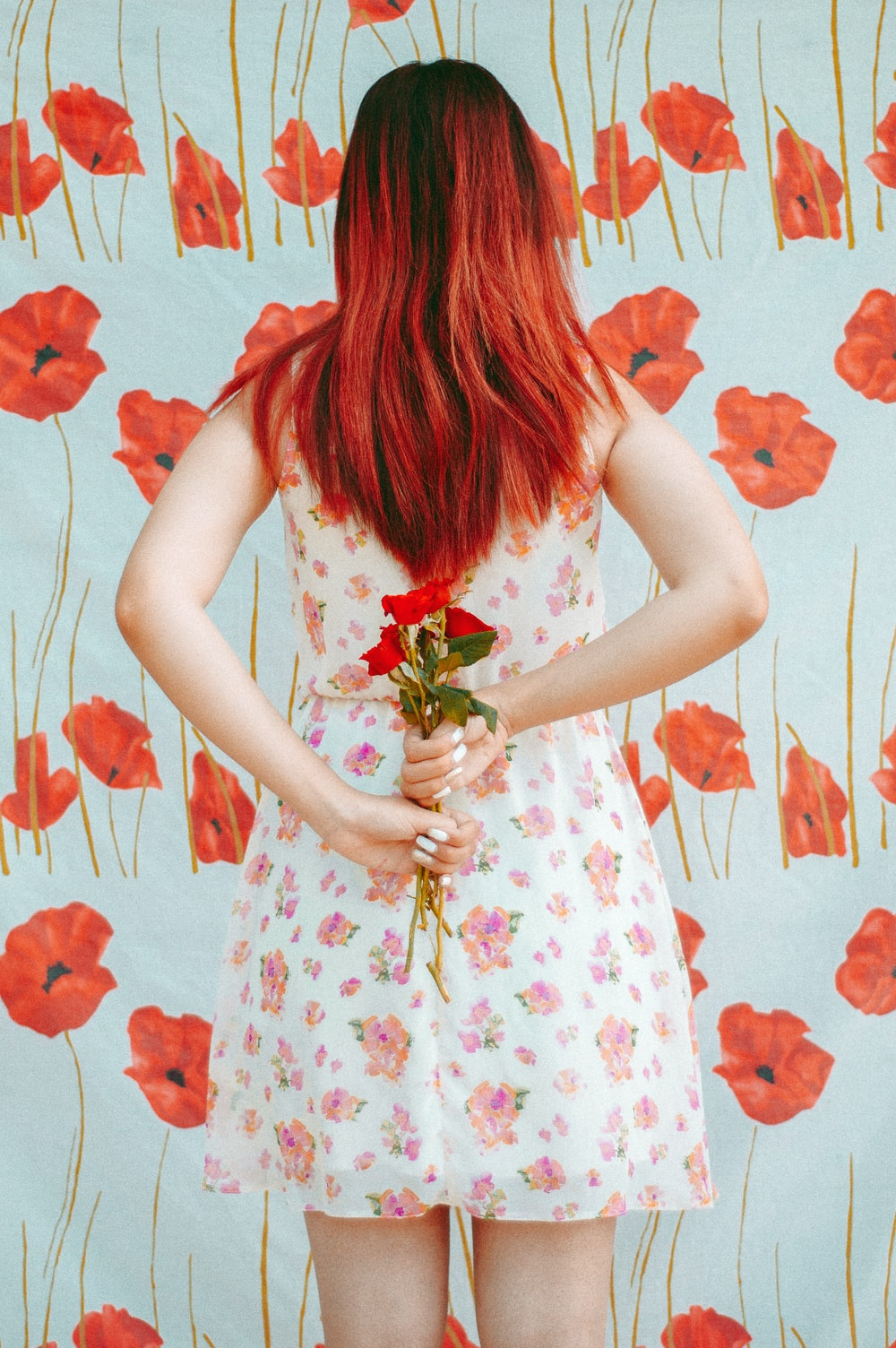woman hides red roses from her back