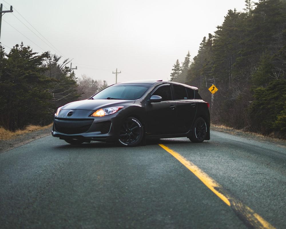 black Mazda 5-door hatchback in middle of road
