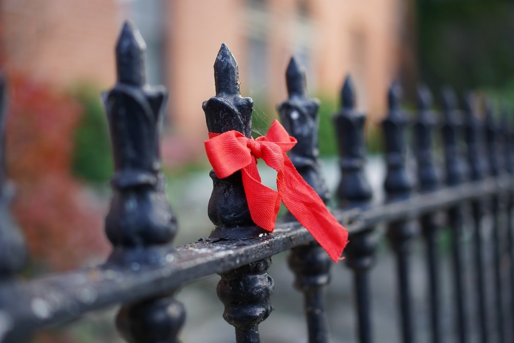 black metal fence with red ribbon