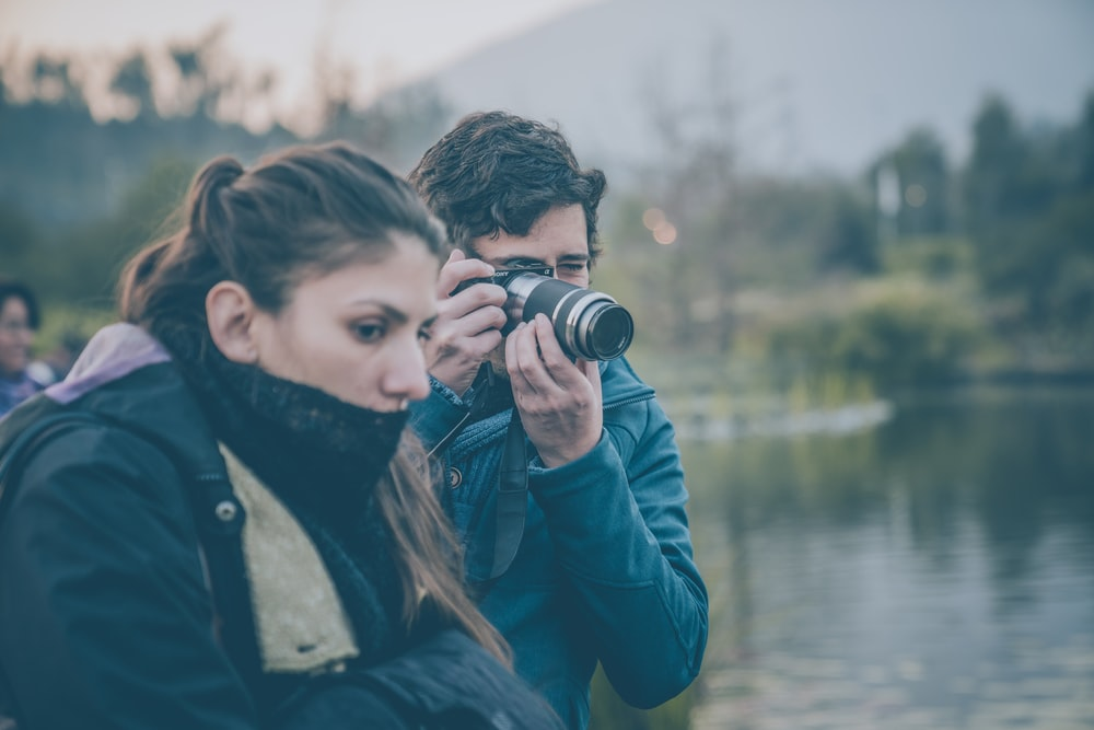 man and woman beside body of water