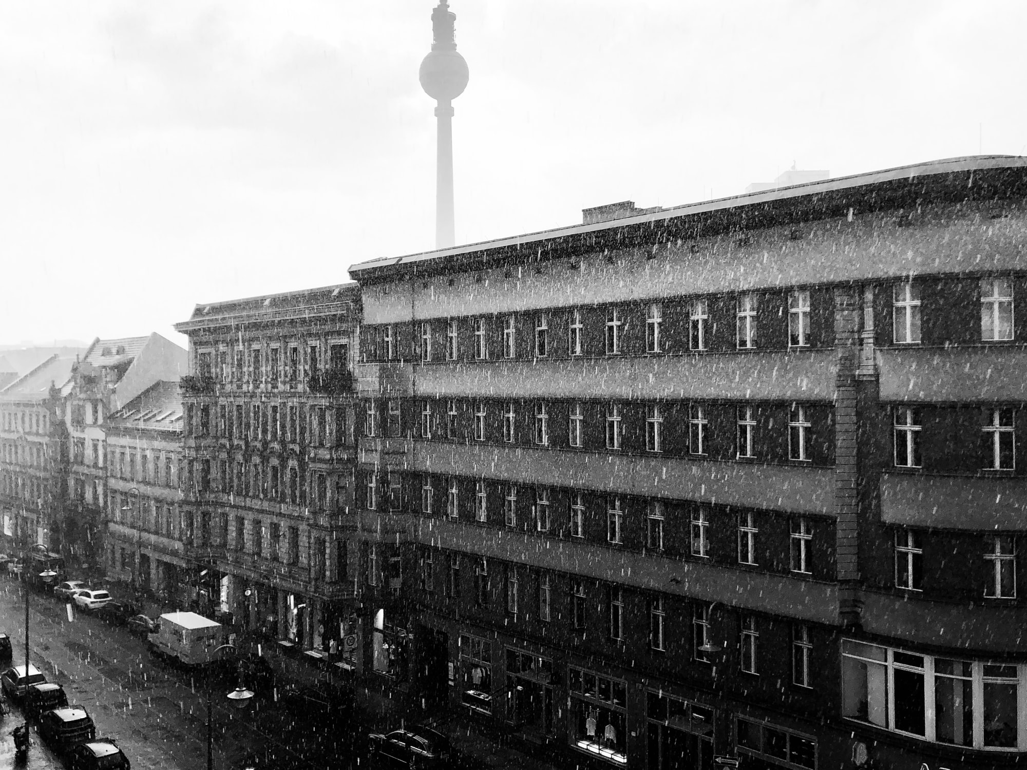 Black and white image of Berlin on a snowy day. The Berlin TV tower is in the background.