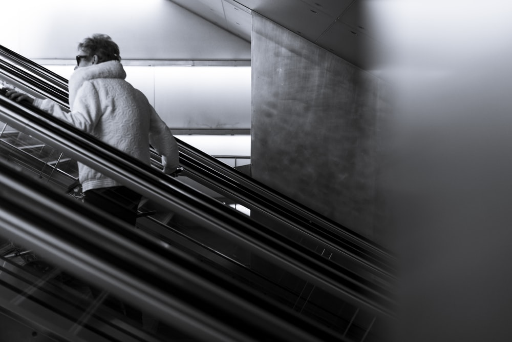 grayscale photography of man walking going up