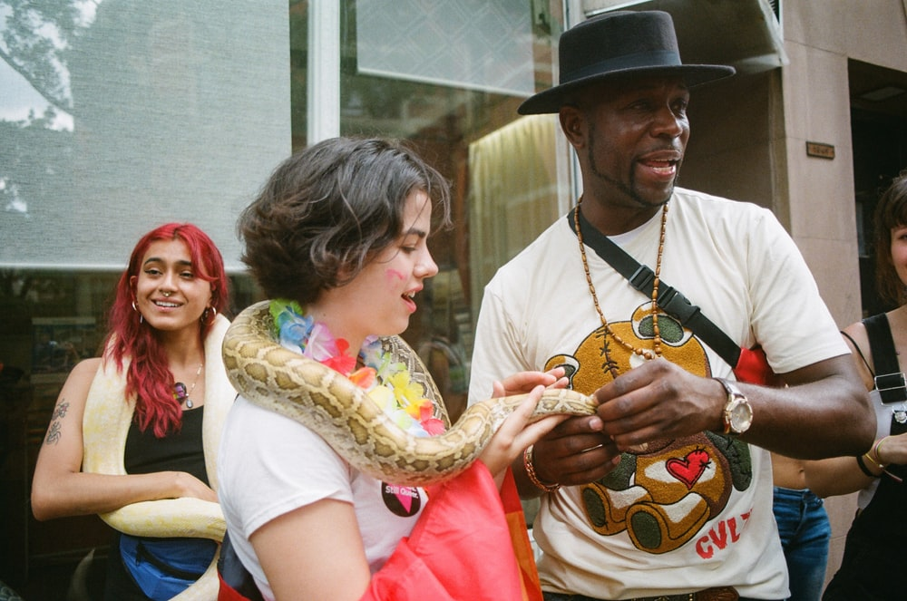 woman standing and holding snake during daytime