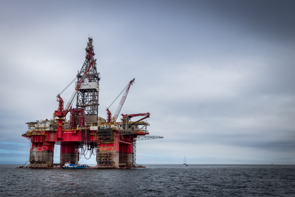 red and grey oil platform in sea