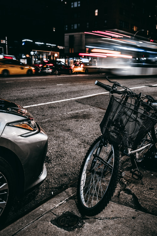 grey and black bike parked in sidewalk