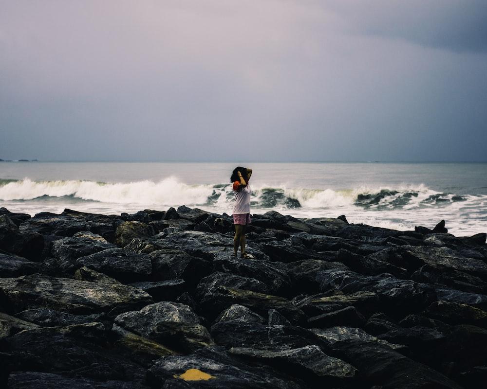 woman standing on rocks near beach