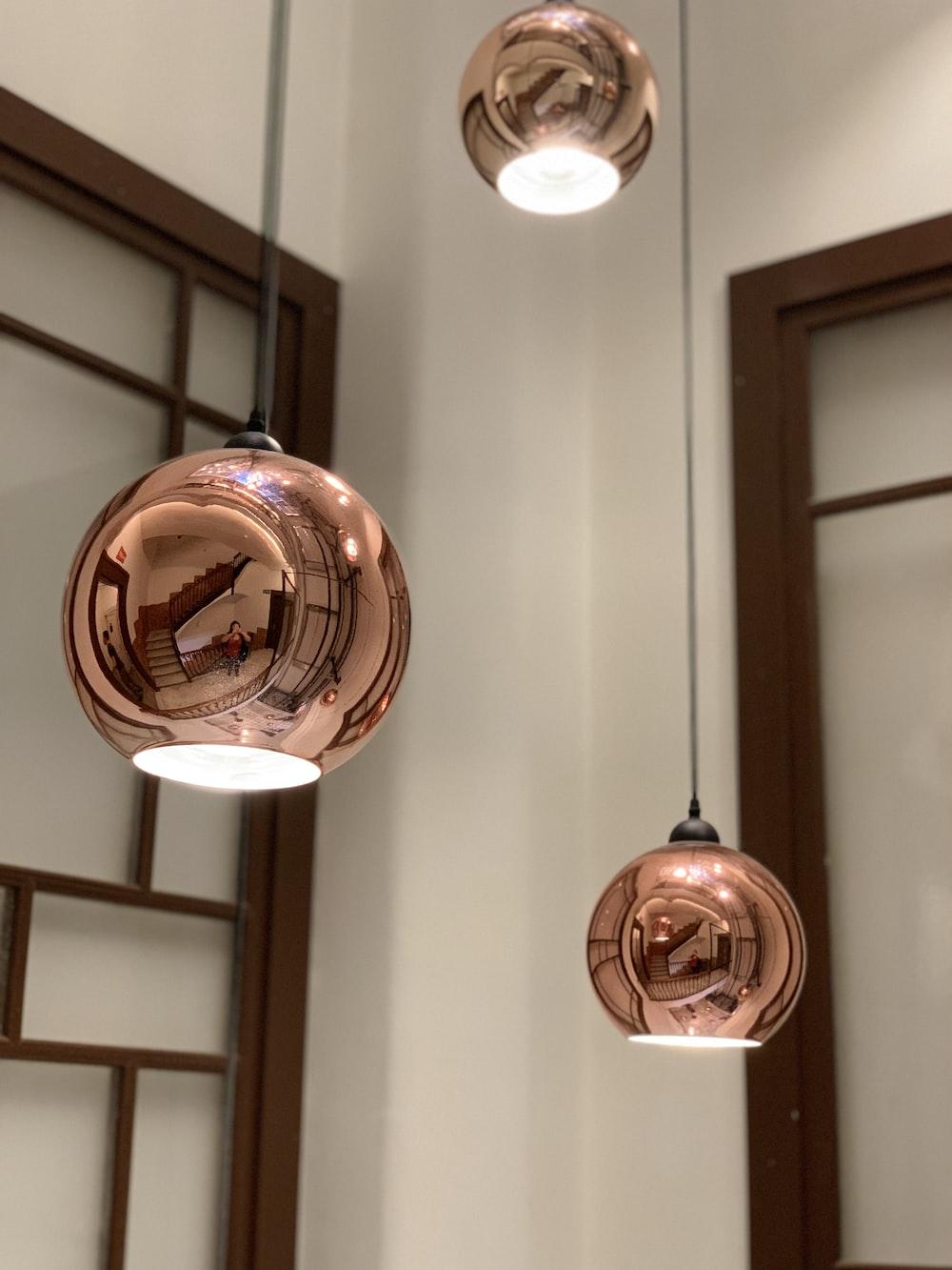 three gold pendant lamps
