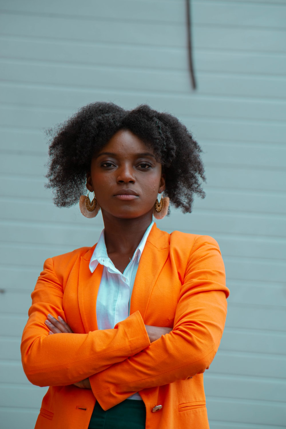 woman in orange blazer standing
