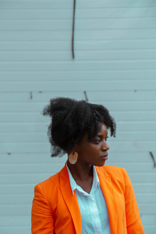 woman wearing orange blazer standing near white wall