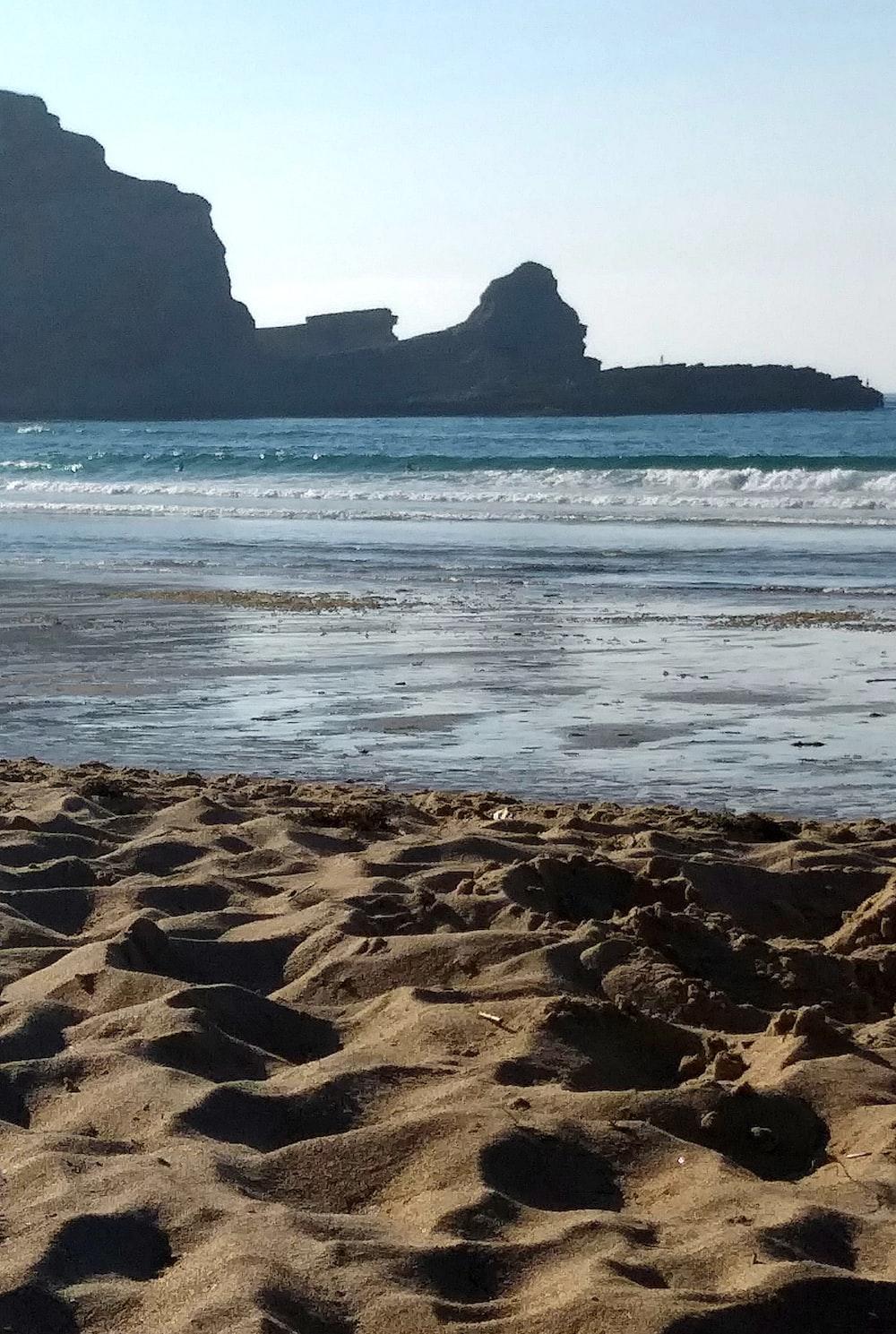 brown sand near seashore and rocks