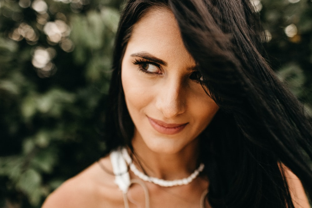 close-up photo of woman wearing white beaded necklace
