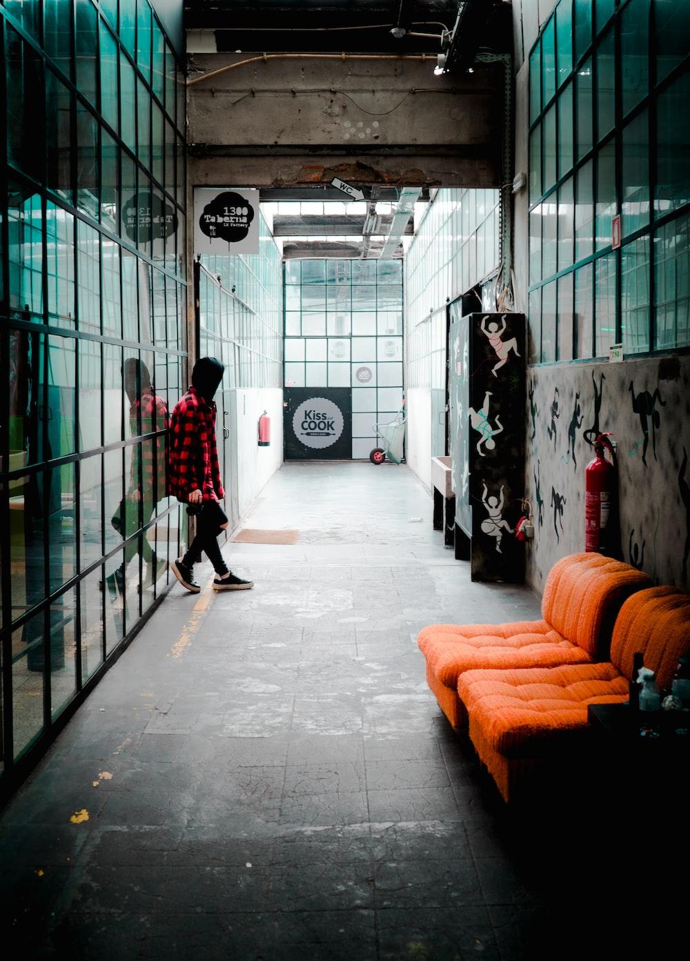 person standing near tufted orange sofa