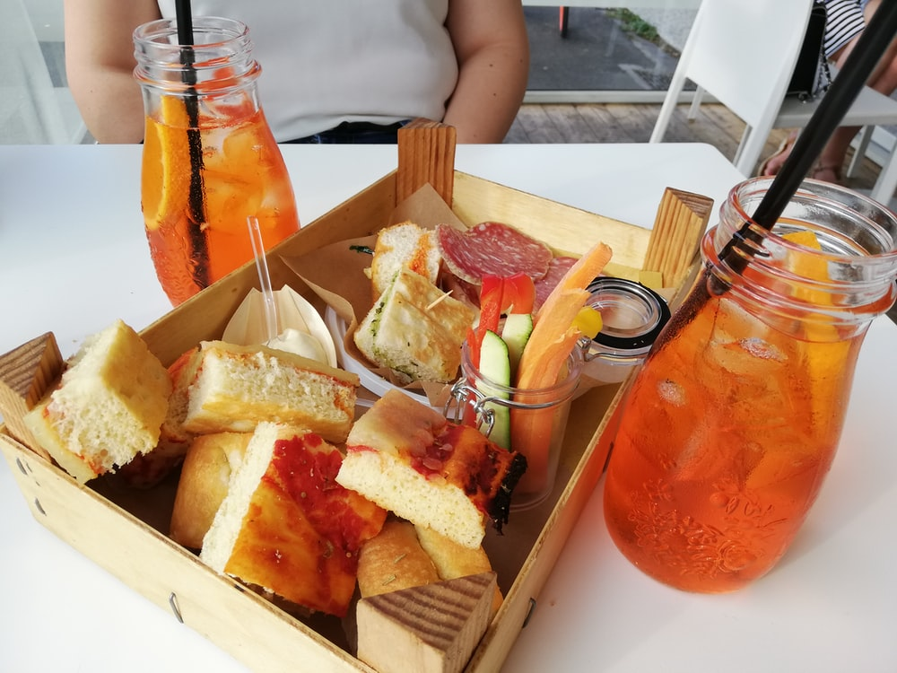 box of comfort food on table with glass of juices